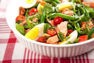 A salad of raw vegetables with eggs and salmon.