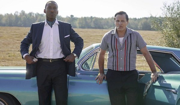 Green Book Mahershala Ali and Viggo Mortensen standing in a field in front of their car