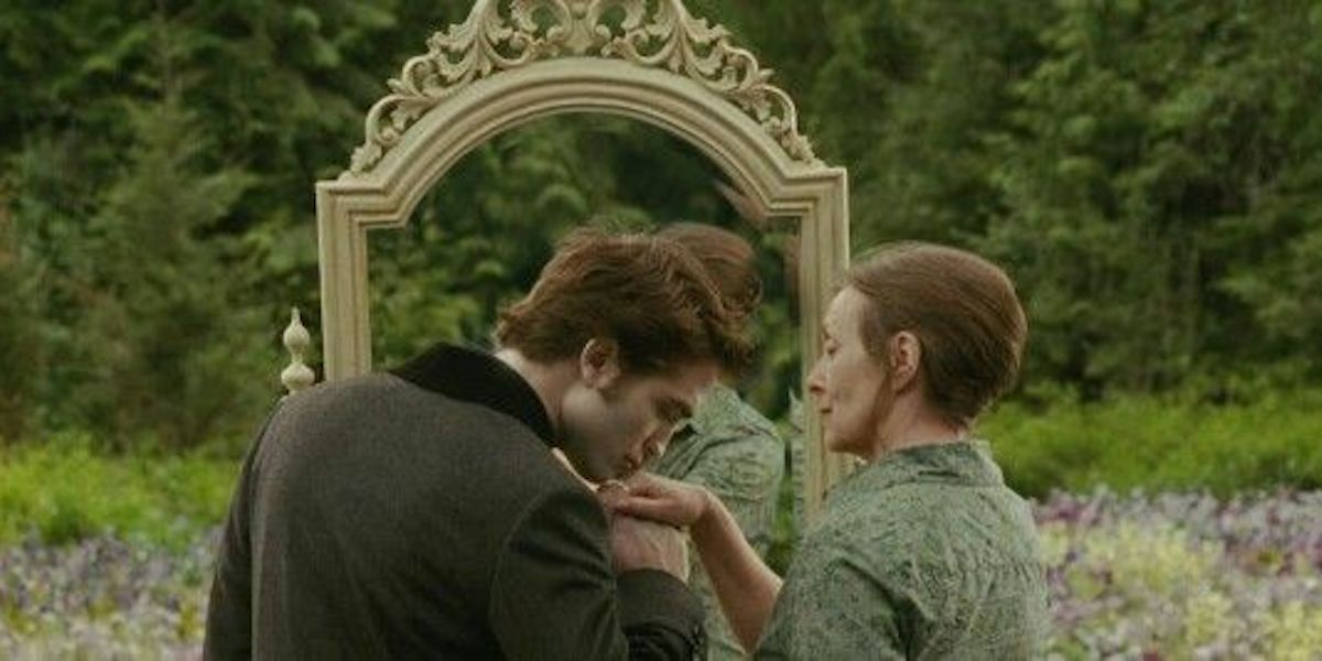Robert Pattinson as Edward Cullen kissing the hand of Bella Swan as an old lady in a Twilight: New Moon dream sequence