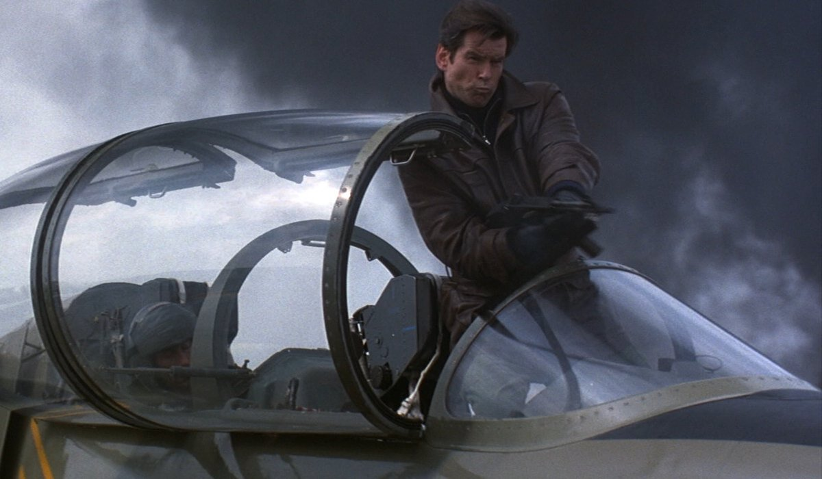 Tomorrow Never Dies Pierce Brosnan shooting while standing in a cockpit