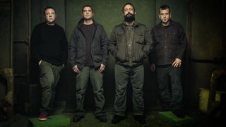 Clutch standing in a dark, green-walled room.