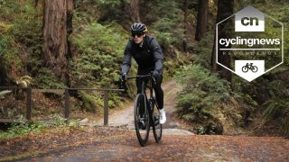 Cyclist wearing a pair of the best leg warmers for cycling rides through a forest on a gravel bike