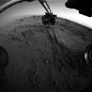 This image shows the view from NASA's Mars rover Curiosity after it uses an autonomous proximity placement technique to place its tool-laden robotic arm on a rock science target called 'Darwin' during the 399th Martian day, or sol, of its mission. Image r