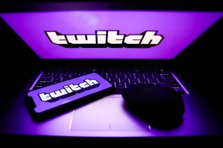 A laptop and phone displaying the Twitch logo.