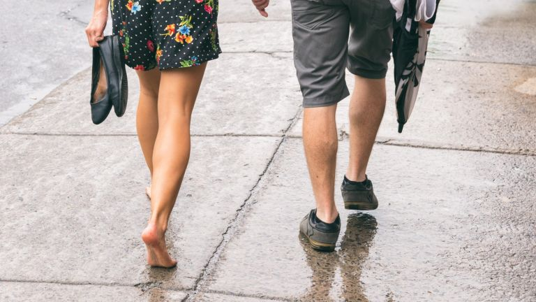 Why walking barefoot is good for you, Couple on the street under the rain, woman walking barefoot