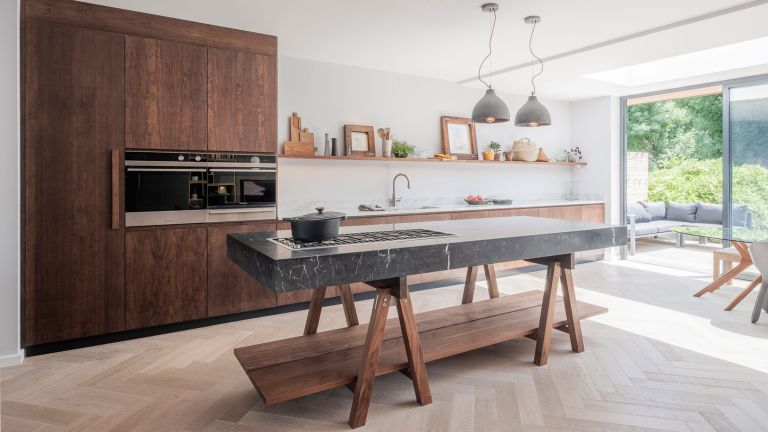 a modern dark wood kitchen with freestanding island with marble slab and open shelving by Naked Kitchens