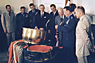 Gen. Thomas White (at right) presents the American flag flown on board the Discoverer XIII reentry capsule to President Dwight Eisenhower at the White House on Aug. 15, 1960.