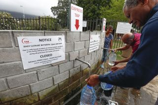 Residents of Cape Town collect drinking water from a mountain spring collection point on Jan. 19, 2018.