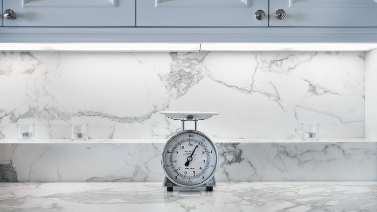 a marble countertop in a kitchen with weighing scales