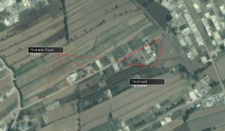 This image shows Osama bin Laden's refuge home with no apparent structural damage, the remains of an unidentified helicopter within the compound perimeter and four evenly spaced road blocks on the road leading to the property.