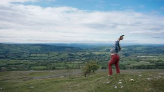 Beautiful woman holding her arms in the air, Black Mountains, Powys, Snowdonia, Wales, UK.