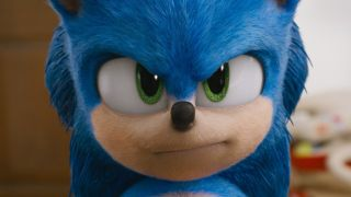 Sonic staring down Tom Wachowski in the kitchen as the two face off after Tom finds Sonic in Sonic the Hedgehog