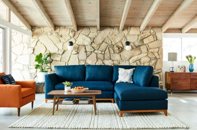 A navy blue sleeper sofa in front of an exposed stone wall