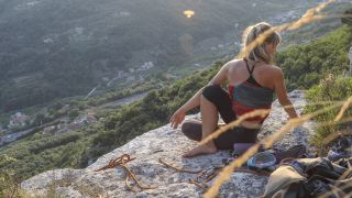A woman climber does a yoga pose on a cliff edge