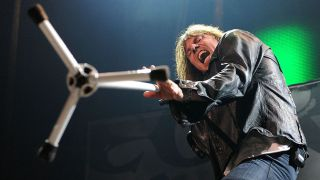 Action stage shot of Joey Tempest attacking a photographer with a mic stand