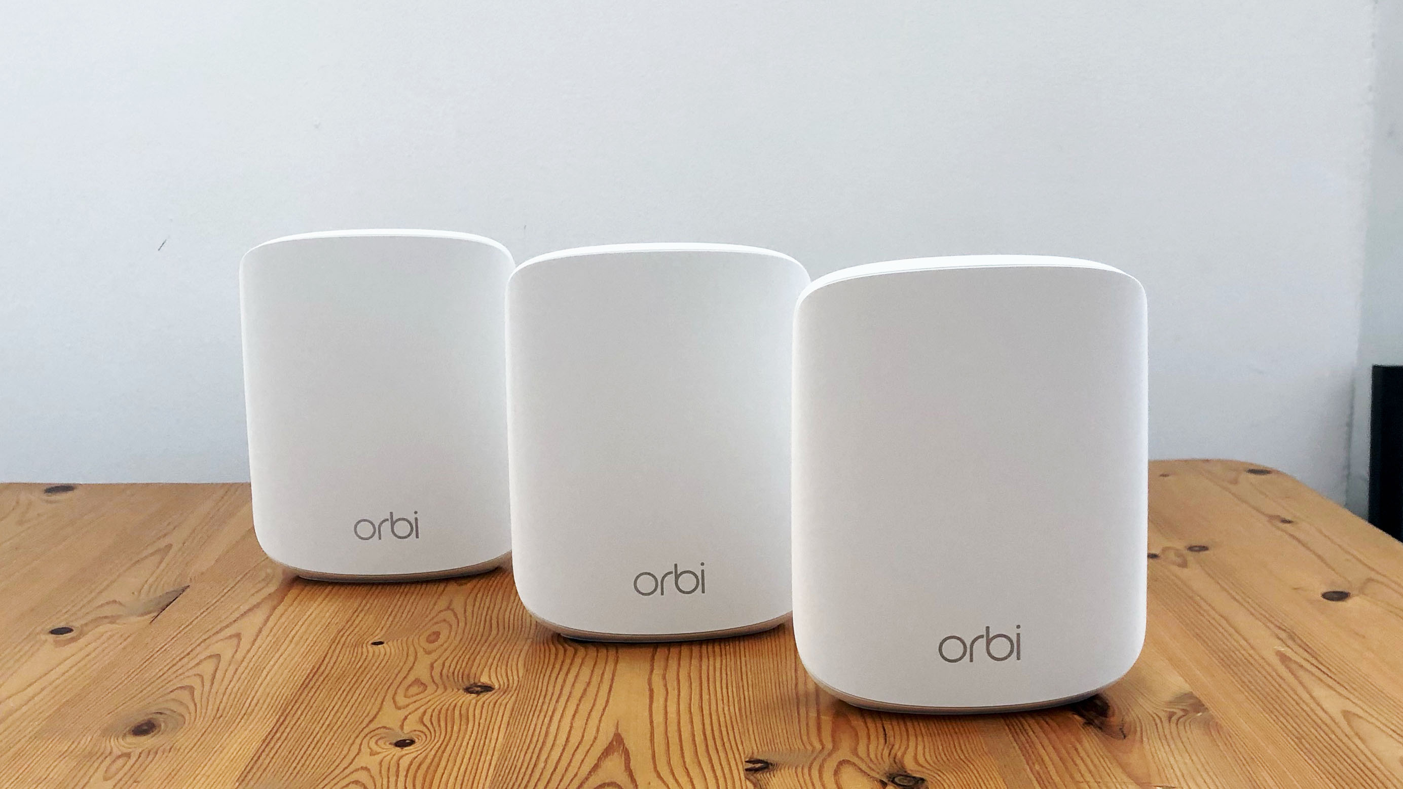 Netgear Orbi RBK353 on a wooden table in front of a white background
