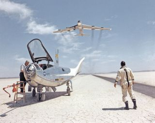 After a research flight by the HL-10 lifting body, technician John Reeves works on the craft, and pilot Bill Dana watches the B-52 that launched it.
