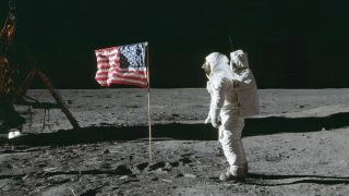 NASA astronaut Edwin (Buzz) Aldrin Jr stands beside the United States flag during Apollo 11 during a moon walk.