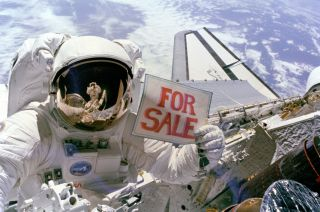 "Astronaut Dale Gardner holds up a ""For Sale"" sign, referring to the two satellites, Palapa B-2 and Westar 6, that they retrieved from orbit. Astronaut Joseph Allen IV is reflected in Gardner's visor."