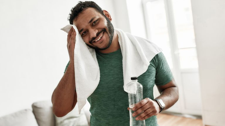 Man toweling his sweaty forehead and drinking water as part of his post-workout recovery