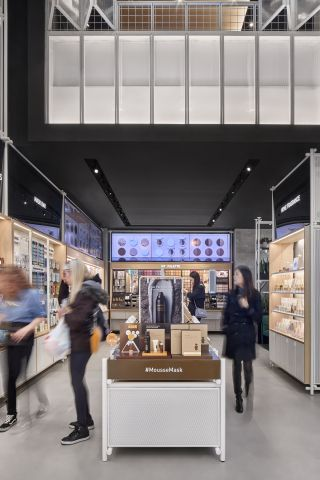 """NEC displays are used to lure shoppers to explore a """"make your own cosmetic palette"""" color wall in the back of the store."""