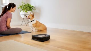 These Roomba deals save you $100, but they won't be around for long: Image shows dog and woman with a robot vacuum
