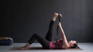 A woman does a yoga pose to stretch her hamstrings