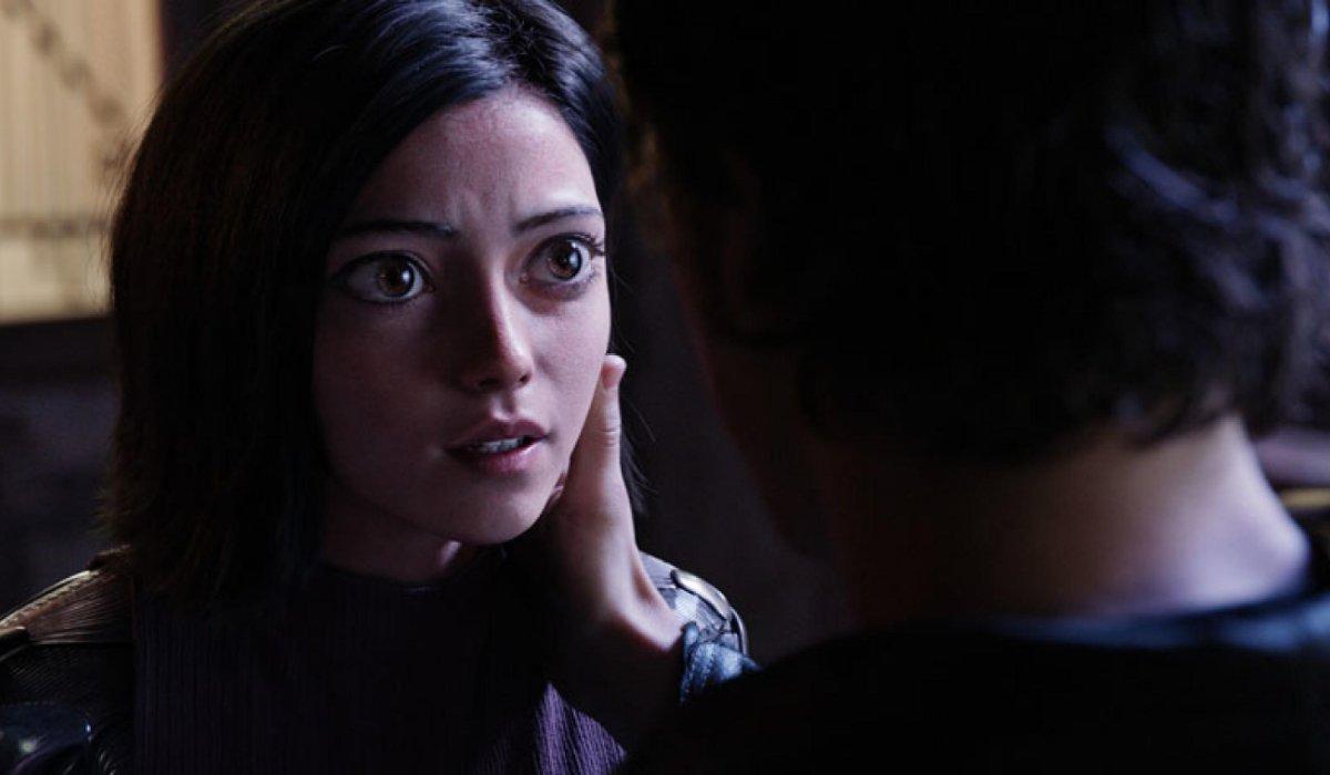 Alita: Battle Angel Hugo holds Alita's face in his hands