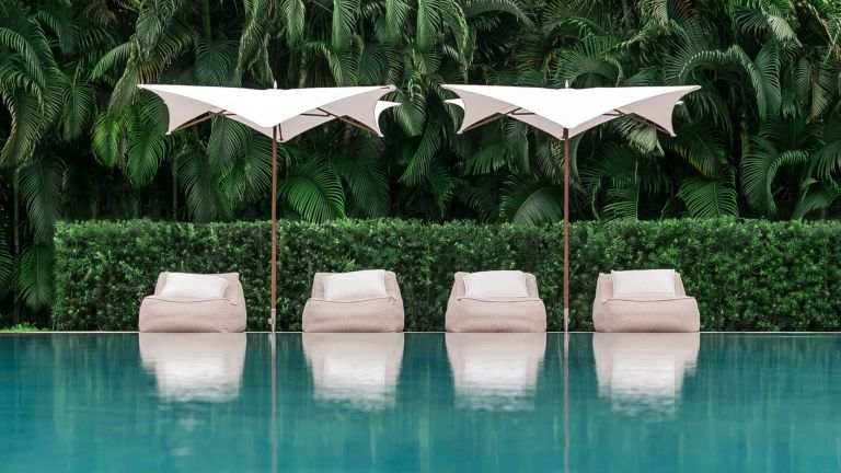 Best patio umbrellas Two white patio umbrellas shading four sun loungers by the side of a turquoise blue swimming pool with lush green tropical foliage in the background