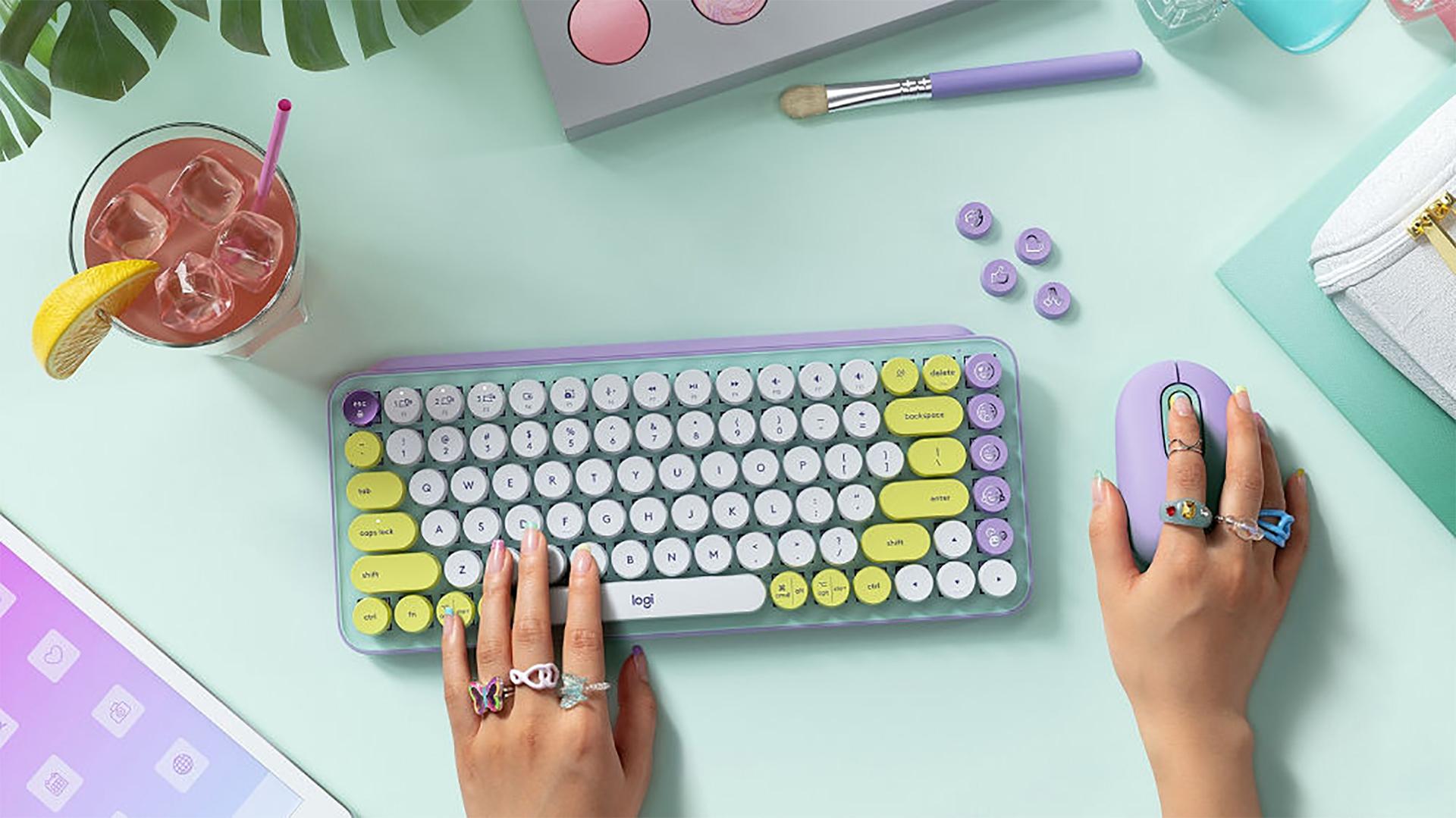Logitech Pop Keys Emoji keyboard on a desk with a user resting their hand on the keys