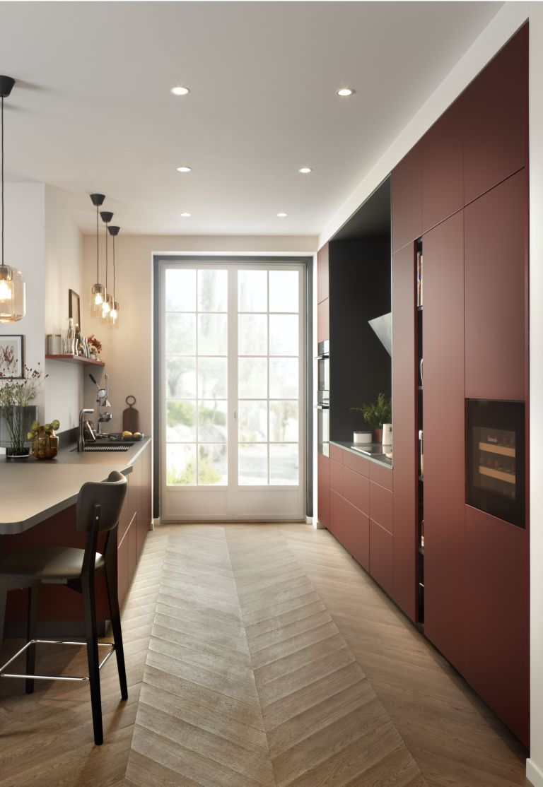 A red galley kitchen with slim french doors, herringbone flooring, sleek handleless cabinets and breakfast bar