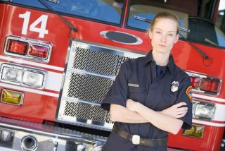 female firefighter stands in front of fire truck.
