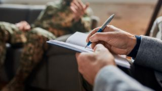 therapist taking notes, man in military uniform sits on couch behind