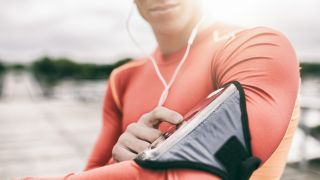 A woman looking at a running app on her smartphone