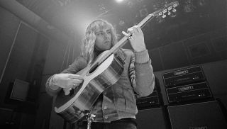 Alex Lifeson plays an acoustic guitar in the studio