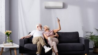 Best ductless air conditioners 2021: Image shows couple sat on a sofa smiling at each other