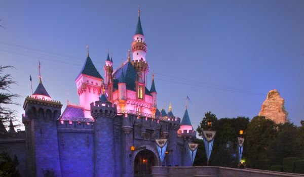Sleeping Beauty's Castle at Disneyland lit up at dusk