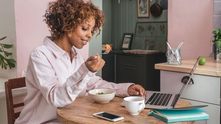 Woman eating brain power foods whilst she works