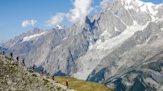 A group of trail runners running across a mountain