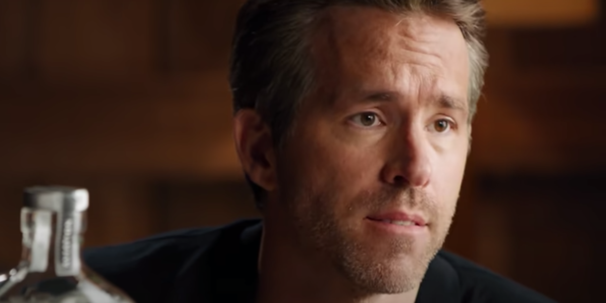 Ryan Reynolds is seated next to a bottle of Aviation American Gin in a commercial.