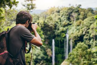 Man photographing waterfalls in the distance