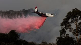 image of helicopter releasing flame retardant on Australian bushfire