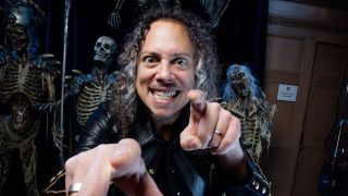 A photograph of Kirk Hammett in front of some creepy skeletons