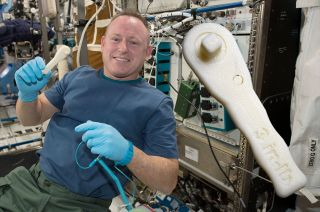International Space Station commander Butch Wilmore shows off the ratchet wrench made with Made In Space's 3D printer on the station. The same wrench can now be printed at home.