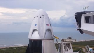The crew access arm swings away from the Demo-2 SpaceX Crew Dragon capsule on May 27, 2020. Bad weather nixed a planned liftoff on that day.