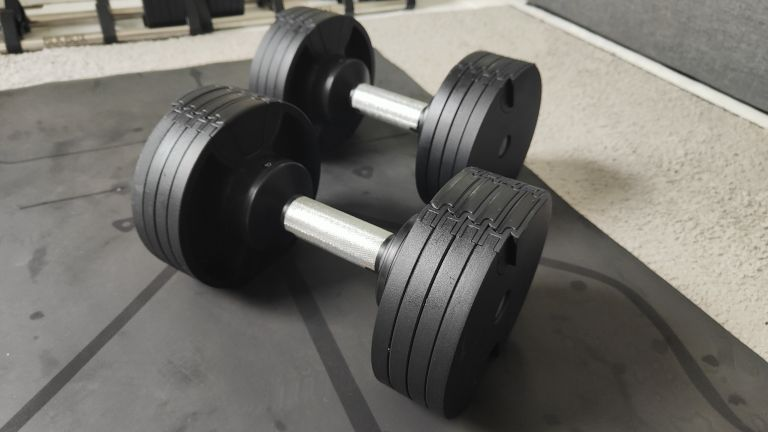 Closeup of the BLK BOX Adjustable Dumbbell on a carpeted floor