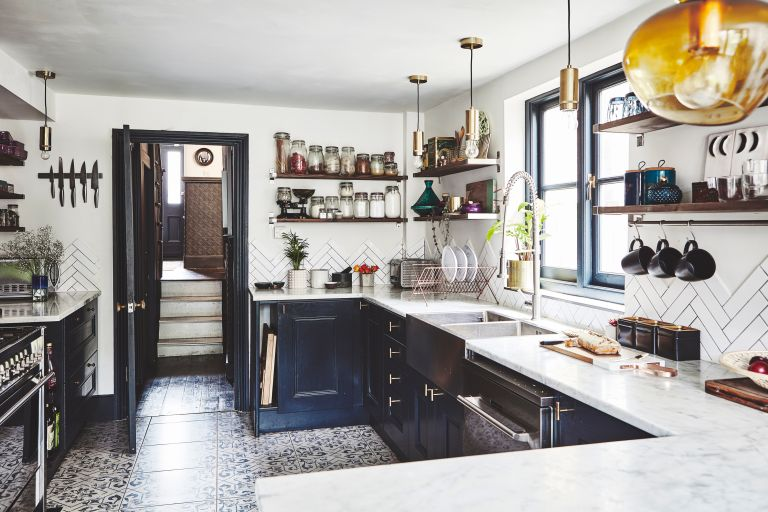 Renovated kitchen in a Victorian house, with dark cupboard doors, marble surfaces and tiled floors