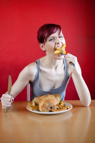 Skinny woman with a whole chicken on her plate stuffing herself with french fries.