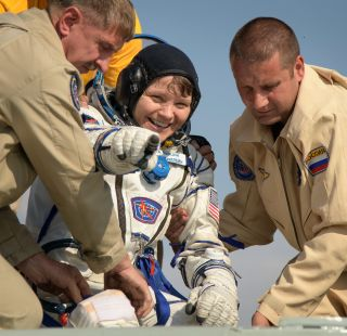 NASA astronaut Anne McClain is assisted out of the Soyuz MS-11 that returned her and crewmates Oleg Kononenko of the Russian space agency Roscosmos and David Saint-Jacques of the Canadian Space Agency back to Earth on June 24, 2019.