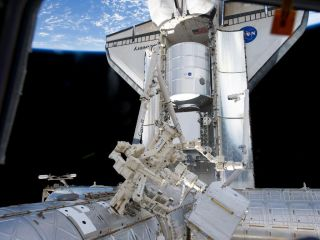 Photo of space shuttle Discovery and the new PMM closet module at the International Space Station